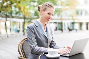 Businesswoman using laptop at cafe photo
