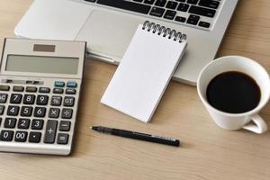 cuaderno de notas en blanco, calculadora, computadora, bolígrafo sobre la mesa