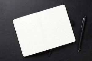 Bloc de notas y bolígrafo sobre escritorio de cuero de oficina
