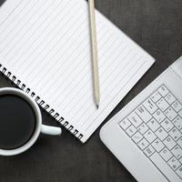 Bloc de notas en blanco, portátil y taza de café