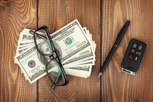Geld, Brille und Autoschlüssel auf Holztisch