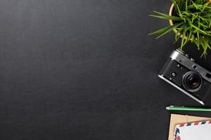mesa de escritório com flor, câmera e suprimentos
