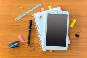 Tablet and notebook on wooden table photo