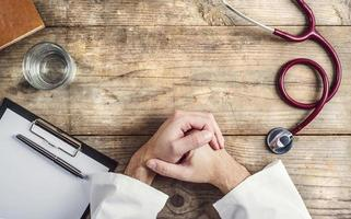 A wooden desk with clipboard, folded hands, and stethoscope photo