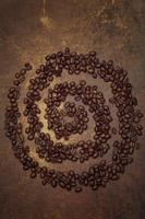 Dark roasted coffee beans arranged in a spiral formation