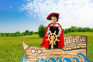 niño como pirata se encuentra en el barco y sostiene el timón