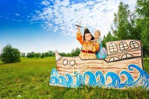 niño como pirata y princesa niña de pie en el barco
