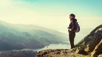 Excursionista en la cima de la montaña disfrutando de la vista, Loch Katrine, Escocia