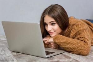 hermosa mujer joven relajada tirado en el piso usando laptop foto