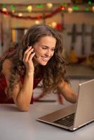 mujer joven feliz que tiene chat de video en la computadora portátil en la cocina
