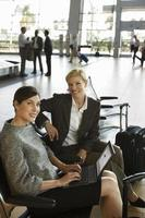Two businesswomen waiting in airport departure lounge, woman usi