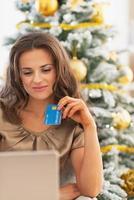Mujer joven con tarjeta de crédito y portátil cerca del árbol de navidad