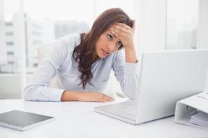 Stressed businesswoman working at her desk photo