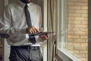 Businessman taps digital tablet computer