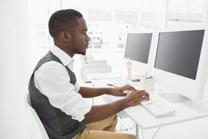 Classy businessman concentrating and using computer photo