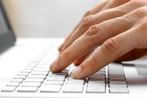dedos escribiendo en la computadora portátil blanca foto