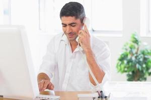 Businessman using telephone and computer photo
