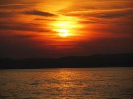 Puesta de sol sobre el agua, el lago de Garda, Italia, el cielo está ardiendo