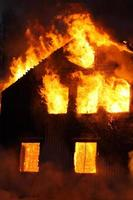 A burning house with flames coming out of the windows photo