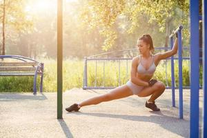 Fitness girl doing stretching exercises in the summer outdoor photo