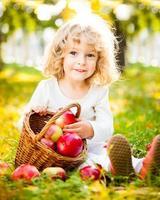 una joven con una cesta de manzanas en el parque