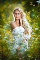 sensual joven rubia con camisa blanca en bosque