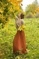 Young beatiful woman collecting autumn maple leaves photo
