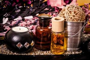 candle and oils with pink flowers spa concept photo