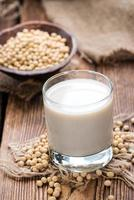 Glass of soy milk with some soy beans