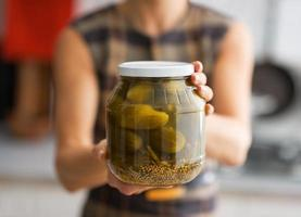 Primer plano de joven ama de casa mostrando tarro de pepinos en vinagre foto