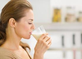 jovem mulher bebendo leite na cozinha
