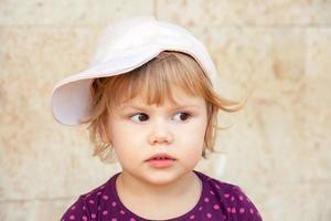 Caucasian blond baby girl in baseball cap photo
