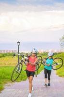 Retrato de jóvenes deportistas caucásicas hacer ejercicio con bicicleta afuera
