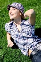Young caucasian girl sitting on the green grass photo