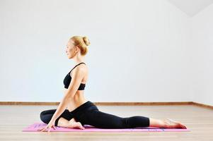 Beautiful caucasian woman exercising yoga indoors