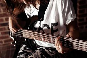 Teenage caucasian puk girl sitting and playing bass guitar closeup