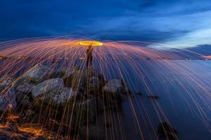 Firework showers of hot glowing sparks from spinning steel wool.