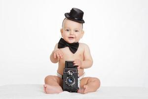 menino caucasiano brinca com a câmera vintage um sorri com alegria