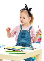 Little girl draws pencils sitting at the table photo