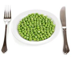 Green peas on plate isolated on white photo