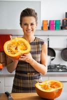 Happy young housewife showing half of pumpkin