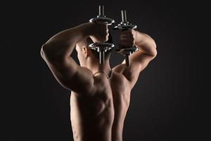 bodybuilder doing exercises with dumbbells photo