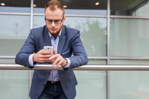 Hombre de negocios caucásico fuera de la oficina mediante teléfono móvil.