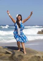 alegre adolescente bailando hula en la playa foto