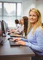 gelukkige vrouw die in computerzaal bij camera glimlacht