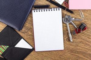 Opened notebook on blank page on wooden desktop background photo