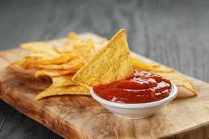 heap of tortilla chips on olive board on wooden table