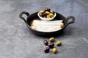 Cheese rolls plate with olives served in a black pan