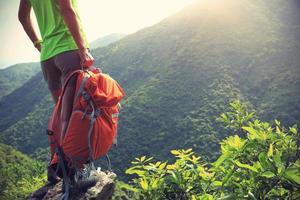 vrouw backpacker geniet van het uitzicht op de bergtop klif