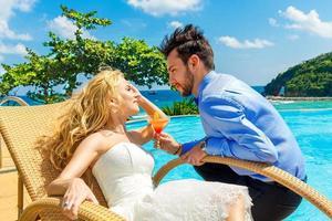 gelukkige bruid en bruidegom genieten van een cocktail oneindigheid bij het zwembad